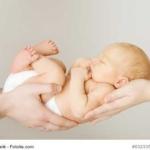 Baby in den Händen der Eltern